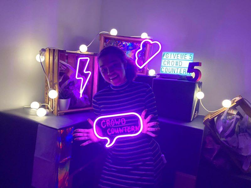 """Auf dem Bild sieht man eine junge Person, die vor einer bunten Kulisse mit pinken Neonfarben steht. Sie hält eine leuchtende Sprechblase mit der Aufschrift """"CROWD COUNTERN"""" in der Hand und schaut lachend in die Kamera. © Servicestelle Jugendbeteiligung e. V., 2021"""