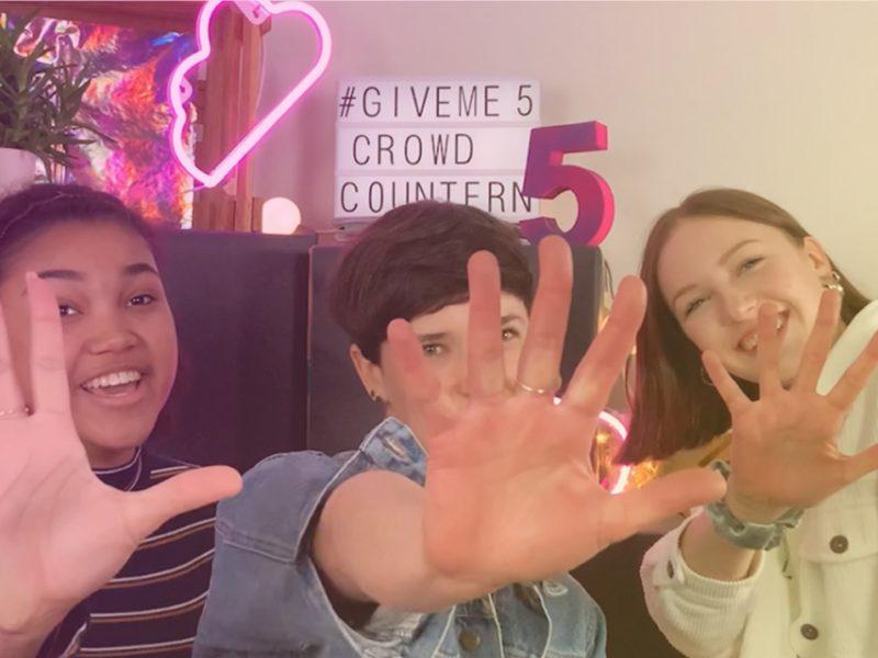 """Das Bild zeigt drei junge Personen, die ihre Hand ausstrecken und damit """"Gegenhalten"""" gegen den Hass im Netzsymbolisieren."""