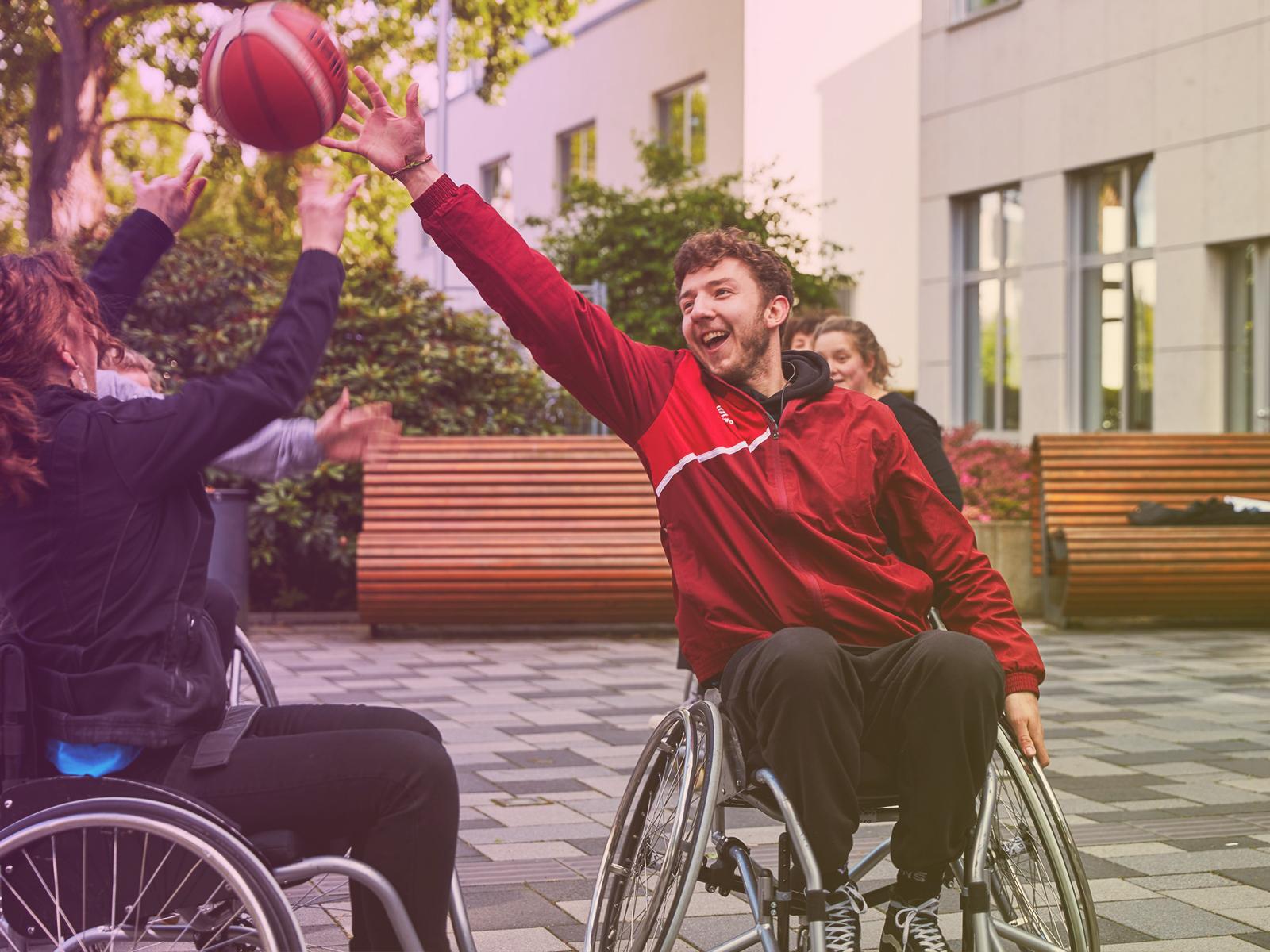 Das Bild zeigt zwei Personen im Rollstuhl, die mit einem Basketball spielen