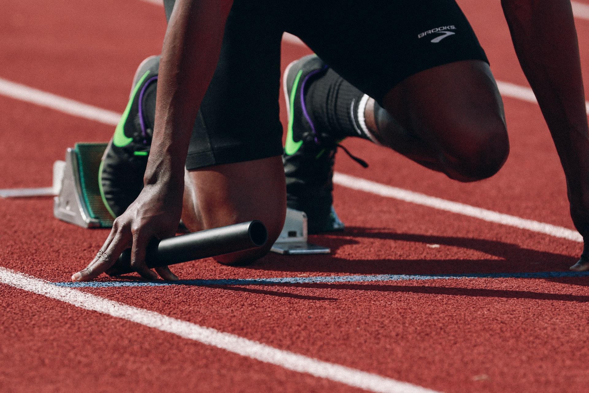 Es sind die Beine einer Person zu sehen, die in einem Startblock steht und bereit ist, loszurennen.